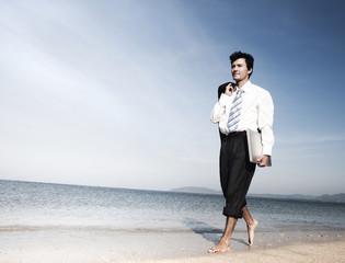 Businessman walking along a beach with laptop