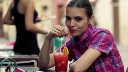 Portrait of beautiful woman drinking cocktail in cafe in city