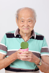 old man hold pot green leaf heart form