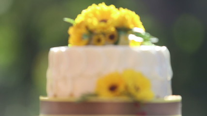 white creamy cake decorated with yellow chrysanthemum flowers