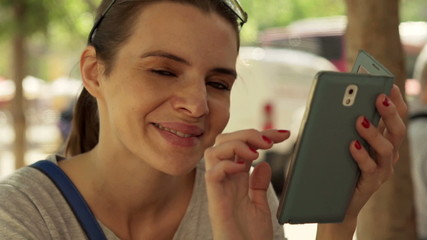 Portrait of happy, pretty woman with smartphone in city