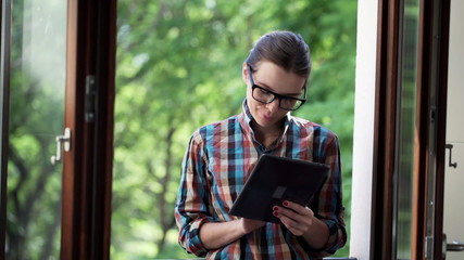 Young geek woman using tablet computer standing on balcony