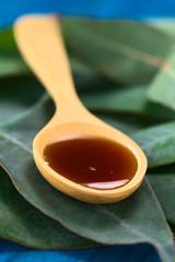 Eucalyptus cough syrup on spoon on Eucalyptus leaves