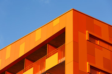 Orange wall and windows of an modern apparment building.