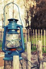 Old blue kerosene lamp hangs on wooden outdoor fence