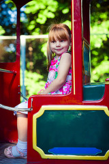 little girl sitting in a small train