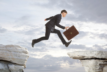 Businessman jumping over rocks