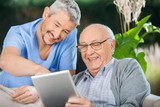 Nurse And Senior Man Enjoying While Using Tablet Computer - 75680948