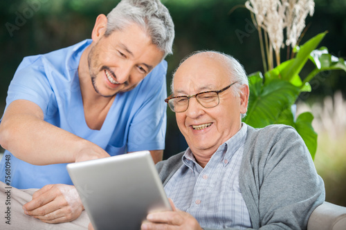Leinwanddruck Bild Nurse And Senior Man Enjoying While Using Tablet Computer