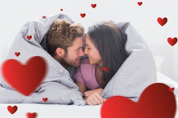 Composite image of couple wrapped in the duvet