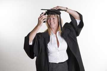 Mature student in cap and gown taking a selfie photo