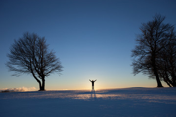 silhouetted man standing in winter landscape