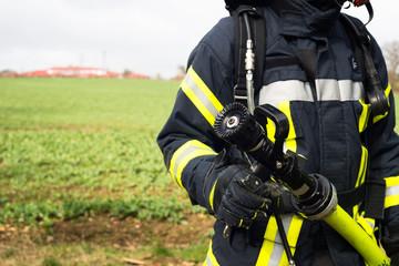 Feuerwehrmann im Einsatz mit Löschschlauch