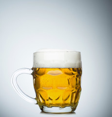 Mug full of fresh beer isolated on white