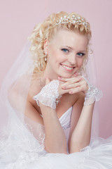 studio portrait of a happy bride on a pink background