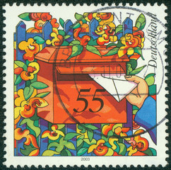 stamp shows hand depositing a letter to a mailbox