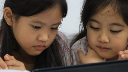 Little Asian girls play looking tablet computer on the bed