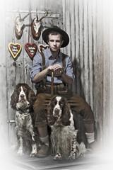 junger Mann in Lederhose mit zwei Hunden
