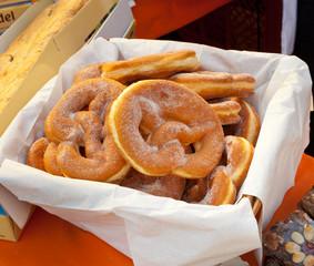 Basket of fried pretzel with sugar.