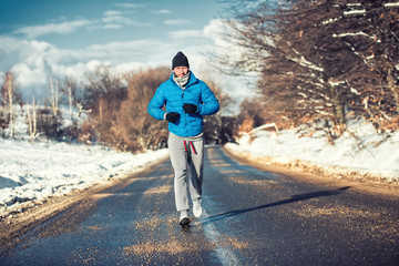 Muscular athlete man jogging on snow, training for box practice
