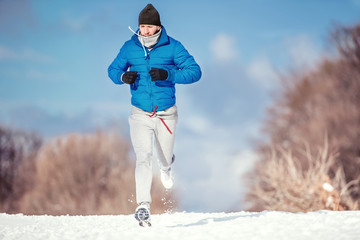 Fitness concept of a man running outdoor in snow on a cold day
