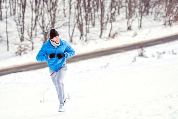 Young athlete man running on snow for a healthy training