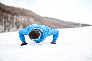 Outdoor training with athlete doing push ups on snow