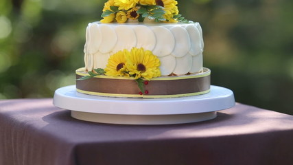 white creamy cake decorated with yellow chrysanthemum flowers