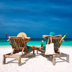 Couple in green relax on a beach at Maldives