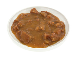Plate of roast beef in gravy on a white background
