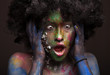 Close up portrait of young woman in afro wig and face art