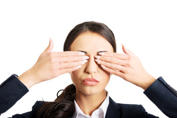 Businesswoman covering eyes with hands
