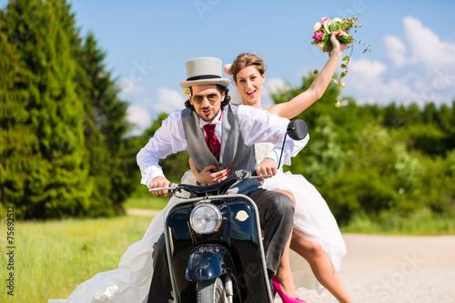 Leinwanddruck Bild Hochzeitspaar fährt Motorroller in Hochzeitskleid und Anzug