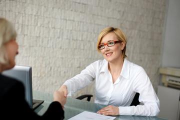 Young blonde businesswoman handshake