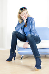 woman wearing blue clothes sitting on sofa