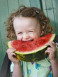 Laughing little girl eating watermelon