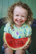Funny laughing  little girl eating watermelon
