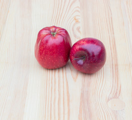 Two red apples on a wooden background