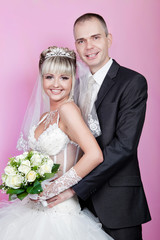 groom and bride with a bouquet  in studio on a pink background