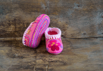 baby pink slippers  on the wooden background