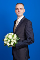 elegant groom holding flowers in a studio on the blue background