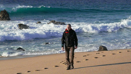 Man Walking on Beach with Waves in the Background, slow motion