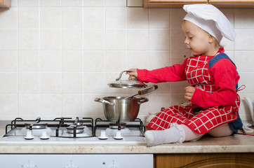 Little cook opens the pan with food