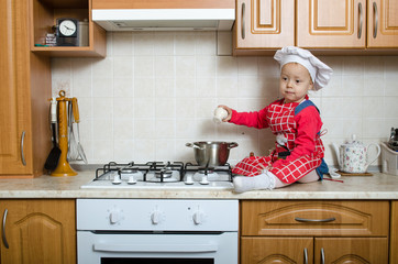Little cook adds salt to the soup