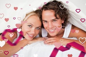 Composite image of couple under a duvet