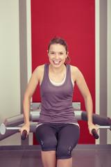 lächelnde frau trainiert an sportgerät