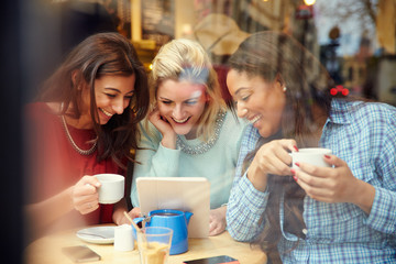 Group Of Female Friends In Caf' Using Digital Devices