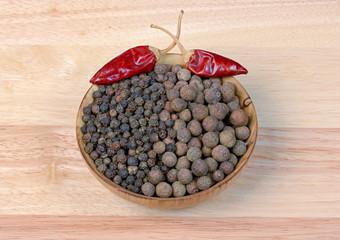 black pepper  in a wooden bowl