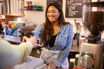 Woman Serving Customer In Coffee Shop
