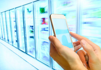 Shopping list on her smartphone at supermarket.